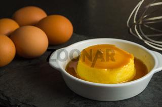 Traditional Brazilian dessert, milk pudding on dark background.