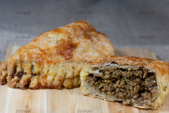 pasties filled with minced meat on a wooden board