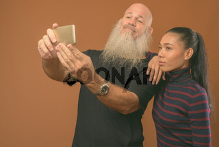 Mature bearded bald man with young Asian transgender woman against brown background