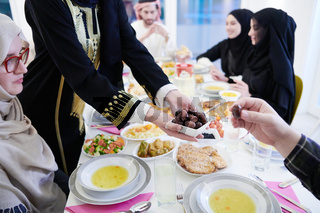 Muslim family having Iftar dinner eating dates to break feast