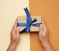 male hands holding gift box with a bow on a brown background