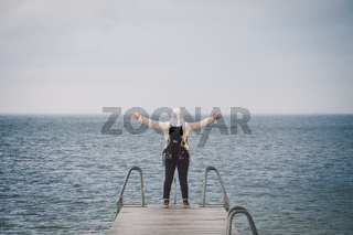 Concept of freedom relaxation. woman relaxing on pier. Backpacker hiker woman with backpack on sea wooden pier stands arms sideways looking to horizon