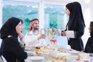 Muslim family having Iftar dinner drinking water to break feast