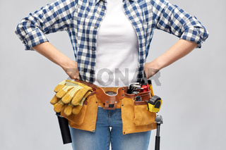 woman or builder with working tools on belt