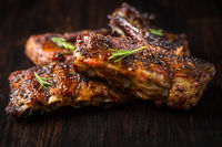 Grilled pork spare ribs with rosemary on wooden background. Barbecue food concept.