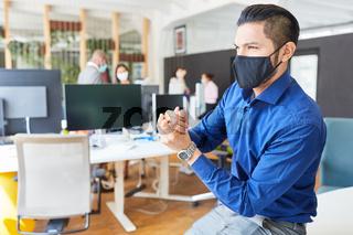 Business Mann beim Hände desinfizieren als Prävention