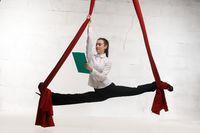Business woman doing splits on cloth shot
