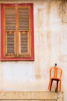 Orange chair hanging on the wall and beautiful wooden window of a traditional house in the old city of Nicosia, Cyprus