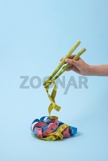 Woman's hand is taking measure tapes by asparagus spears as sticks.