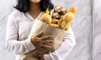 Close up Asian housewife woman hold grocery bread bag.