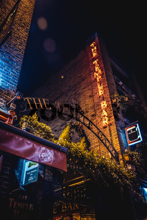 DUBLIN, IRELAND, DECEMBER 24, 2018: Temple Bar historic district, known as cultural quarter with lively nightlife. Nightscene of the bar, full of neon lights and its typically irish pub look.