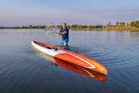 senior male stand up paddler rinsing his paddlebiard