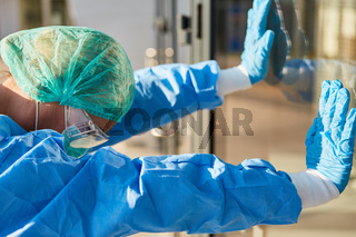 Arzt mit Schutzkleidung bei Coronavirus Pandemie stützt sich an Fenster