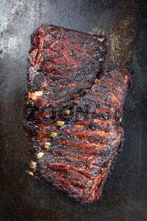 Barbecue veal spare loin ribs St Louis cut with hot honey chili marinade burnt as top view on an old rustic board