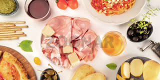 Italian cold cuts overhead panoramic shot. An assortment of hams and cheeses, shot from the top on a white background with wine