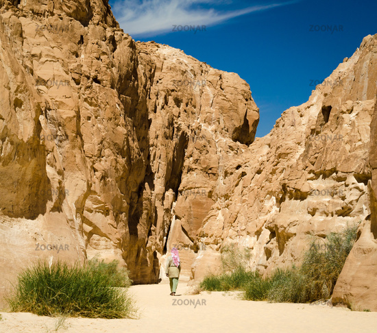 bedouin in white goes in the canyon in the desert among the rocks in Egypt Dahab South Sinai