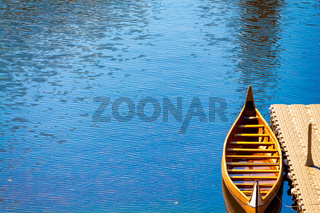 A Wooden Canoe Docked in a River