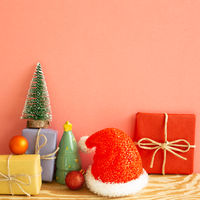 Christmas concept. Gift boxes with fir tree, baubles, santa claus hat on wooden table with coral pink background