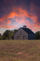 Sunset over a rustic barn in a field on Cape Cod