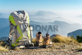 Hiking equipment. Backpack and boots on top of mountain Corno di Tres, Tresner Horn, Trentino, South Tyrol, Val di Non, Val d'Adige, Alps, Italy.
