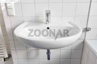 Keramik Waschbecken im Bad mit Wasserhahn und Fliesen