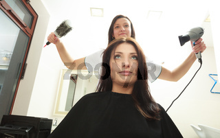 In hairdressing salon. Hairstylist with dryer drying hair of woman client.