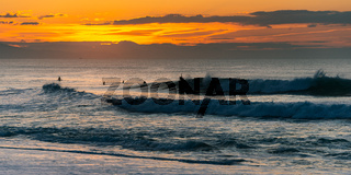Surfers at sunset in Biarritz, France