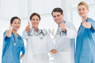 Doctors gesturing thumbs up at hospital