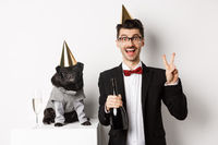 Small black dog wearing party hat and standing near happy man celebrating holiday, owner showing peace sign and holding champagne bottle, white background