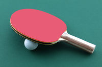 Table tennis bat and white ball on green table ping pong paddle