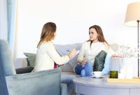 Smiling woman on couch talking with therapist