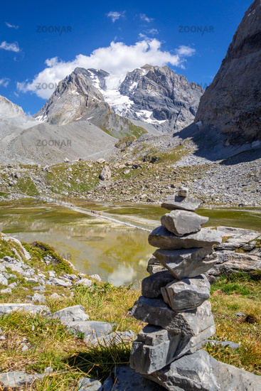 Cairn in front of the Cow lake, Lac des Vaches, in Vanoise national Park, France