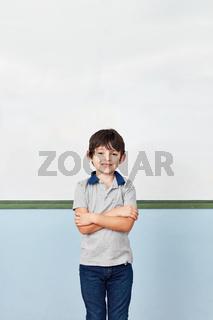 Junge vor Whiteboard in Grundschule lächelt
