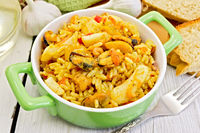 Pilaf with seafood and fork on board