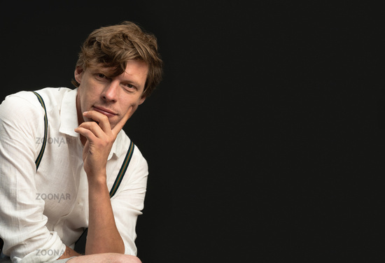 Thoughtful man in white shirt looks at camera against black background. Empty space for text