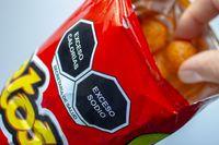 Calgary, Alberta. Canada. Nov 11 2020. Close up to a high sodium and calories warning signs on a bag of cheetos and a person eating.