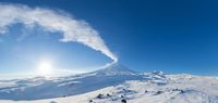 Winter volcanic landscape, panoramic view of eruption active volcano plume gas, ash from crater
