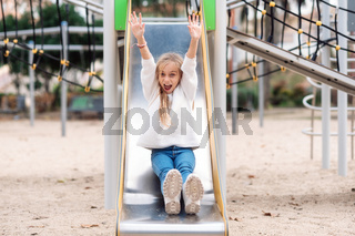 Happy little girl on slide in summer park.