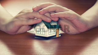 Hands saving small house