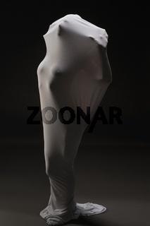 Cry woman under cloth standing in dark studio