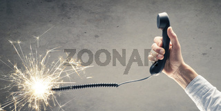 Businessman holds a telephone handset with a burning telephone cord
