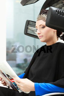 Haidressing salon. Woman dying hair reading magazine. Modern equipment.