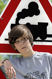 portrait of a cool boy in front of an locomotive traffic sign
