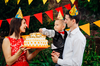 Subject children's birthday party, food and sweets. A young family celebrates one year of son. Dad is holding a big cake, mom is holding a baby in her arms. Baby tastes finger cream on cake with cake