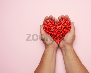 two male hands holding a red wicker heart on a pink background,
