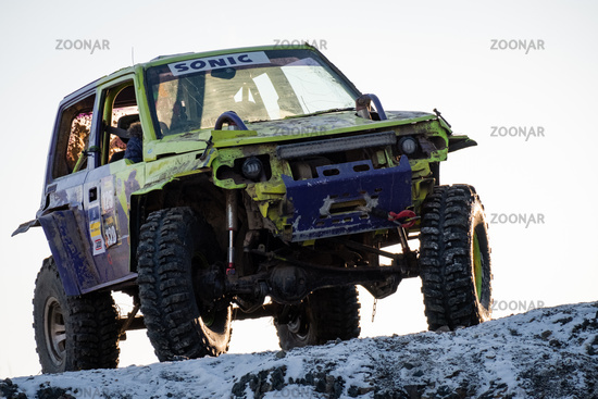 Khabarovsk, Russia - Nov 11, 2019: Jeep Suzuki Jimny overcomes obstacles in the forest. Women behind the wheel of a car.