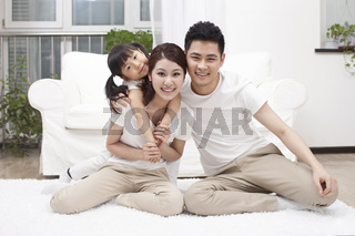 A happy family of three is playing in the living room