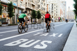 Cyclists riding on an empty Gran Via Avenue during Covid-19 pandemic lockdown in Madrid
