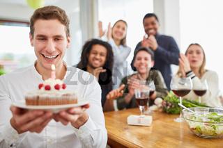 Junger Mann mit Freunden überreicht Kuchen zum Geburtstag