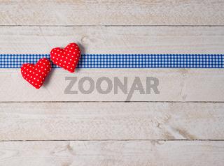 Zwei rote Herzen auf Holzhintergrund